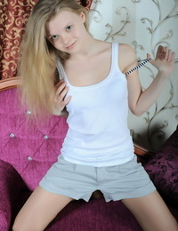 Young looking teen Kisa undresses for nude poses on parlor bench